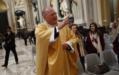 New York Archbishop Timothy Dolan waves as he arrives to lead a mass at St. John Lateran's Basilica in Rome
