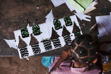 A butterfly wing apprentice makes a mosaic in Bangui, Central African Republic