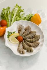 Jumbo headless shrimps with lemon and cherry tomato on white plate