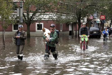 A man carries his dog as people make their way out of the floodwaters in Hoboken, New Jersey