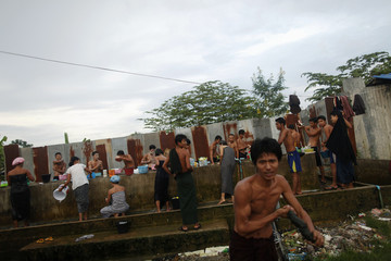 People bathe at a collective housing for migrant workers from Myanmar near Mae Sot in northwest Thailand