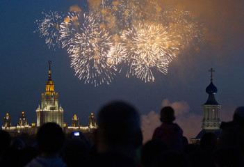 Spectators watch as fireworks explode in the sky above an Orthodox church with Moscow State University main building in the background during a display as part of celebrations for Victory Day in Moscow