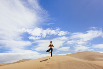 Woman practicing yoga in sands