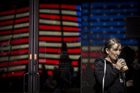 Woman sips an iced coffee drink from Starbucks in front of a reflection of a U.S. flag in Times Square in the Manhattan borough of New York