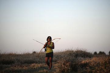 A Guarani Kaiowa girl walks with a bow and arrow on the edge of the ancestral land they call Tekoha Takuara in Juti
