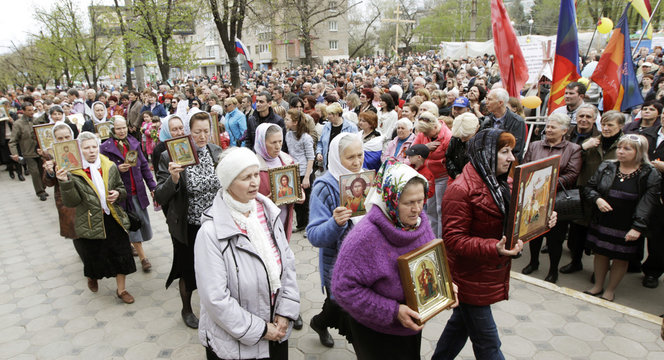 Orthodox believers walk with icons at the seized office of the SBU state security service in Luhansk