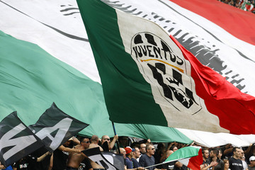 A Juventus supporter waves a giant Italian flag with the club's logo during their Italian Serie A soccer match against Palermo at the Juventus stadium in Turin