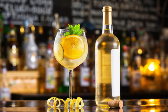 Glass of sangria and white wine bottle at bright bar counter background.