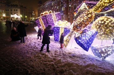 People take pictures of children in front of a Christmas tree and light decorations near Royal Castle at Old Town in Warsaw