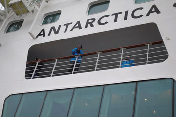 Tourists take pictures from the deck of a cruise ship docked at the port of a research town Ny-Aalesund in the Arctic archipelago of Svalbard
