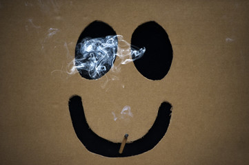 A man smokes a marijuana joint inside a box with a happy face cut out before The Global Marijuana March in Toronto
