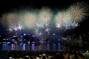 Thousands of people watch as fireworks explode over the Victoria Harbour of Hong Kong to mark China's National Day