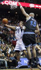 Dallas Mavericks guard Barea shoots under Orlando Magic center Gortat during first half NBA basketball action in Orlando