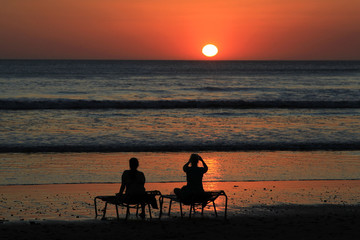 A tourist takes a picture of the sunset at Montelimar Beach on the Nicaraguan Pacific coast