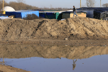 """A migrant walks on top of a pile of sand which separates the road that leads to the ferry terminal and the camp known as the """"Jungle"""", a squalid sprawling camp in Calais"""