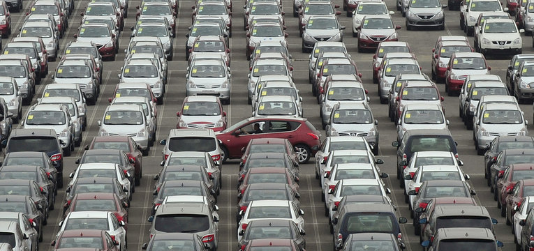 Man drives red car past parking lot where large numbers of newly manufactured cars are parked at Dayaowan port of Dalian