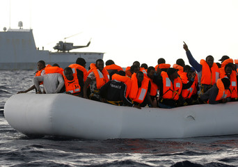 An overcrowded raft carrying African migrants is seen in front of an Italian Navy vessel, as lifeguards from the Spanish NGO Proactiva Open Arms rescue all 112 on aboard, while it drifts out of control in the central Mediterranean Sea