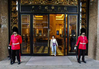 A woman walks out of the door of the Grand Emperor Hotel and Casino between two security guards, in Macau