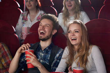 Positive couple of two, boyfriend in checked shirt and girlfriend in gray blouse surprised smiling, watching comedy movie together, holding red cup with cola. Best friends having fun at cinema hall.