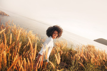 african american young woman having fun outdoors at sunset. laughing girl on field