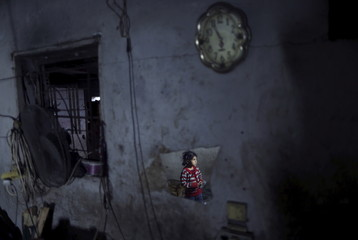 Palestinian girl is reflected in a mirror as she stands at her family's house lit by a torch during a power cut in the northern Gaza Strip
