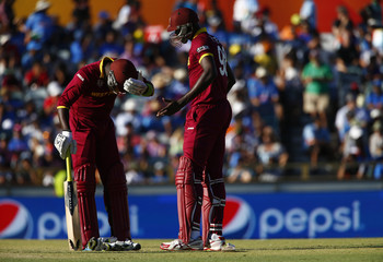 West Indies captain Holder speaks with fellow batsman Sammy after Holder survived a run-out attempt during the Cricket World Cup in Perth