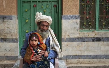 An Afghan migrant sits with his granddaughter at the doorway to his family's dwelling on the outskirts of Peshawar