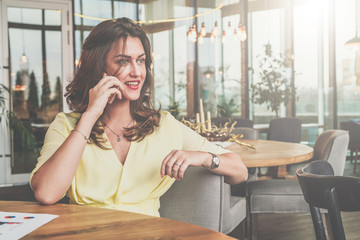 Young attractive businesswoman sitting alone at table in cafe and calling by mobile phone.
