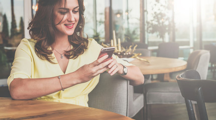 Young smiling businesswoman sitting in cafe at table, using smartphone and looking at his screen. Young woman working