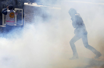 A protester runs away from tear gas fired by Israeli troops during a protest near an Israeli checkpoint in Bethlehem