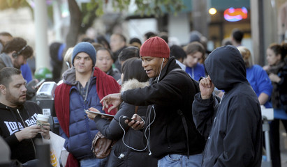 Barry Williams checks his watch while waiting in line for an iPhone 5 shortly before sales commenced in San Francisco