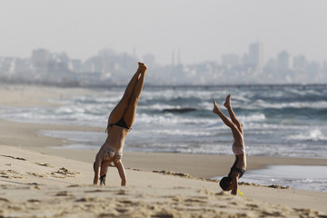 Israeli girls play on Zikim beach at the Mediterranean sea as the northern Gaza Strip is seen in the background