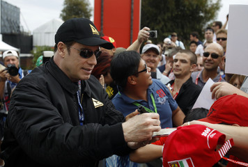 Actor John Travolta signs autographs for fans at the Australian F1 Grand Prix in Melbourne
