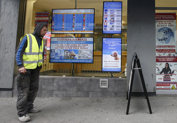 A man looks at available currency exchange rates on a board outside of a bureau de change in London