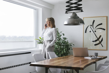 Businesswoman talking on mobile phone in conference room
