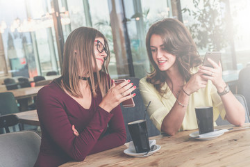 Meeting friends in a cafe. Two cheerful girls sit at a table, drink coffee and discuss news.