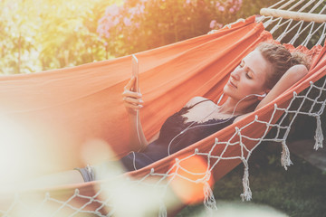 Summer day, young woman lying in orange hammock in park and listening to music on smartphone.