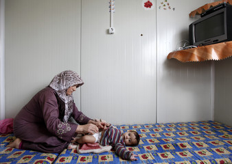 "Syrian refugee woman Havla Araby changes the diaper of her eight-month-old baby Intisar in their family container in a refugee camp named ""Container City"" on the Turkish-Syrian border in Oncupinar in Kilis province"