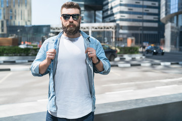 Bearded hipster man in sunglasses, dressed in white T-shirt, stands on city street.Mock up. Space for logo, text, image.