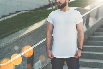 Summer day. Young bearded hipster man dressed in white t-shirt is stands on steps. On background is lawn. Mock up.