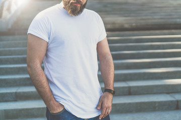 Front view.Young bearded hipster man dressed in white t-shirt is standing on steps with his hand in his jeans pocket. Mock up.