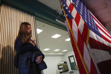 A girl puts her hand over her heart dying the singing of the Star Spangled Banner before the town hall for U.S. Republican presidential candidate and New Jersey Governor Chris Christie at the Hampton Academy in Hampton, New Hampshire