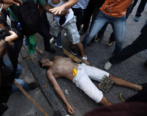 An injured man lies on the ground during a protest against the Confederations Cup and Brazil's government in Recife