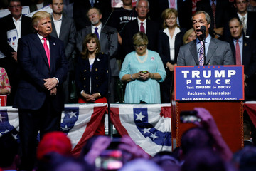 Republican presidential nominee Donald Trump watches as Member of the European Parliament Nigel Farage speaks at a campaign rally in Jackson