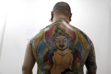 A participant shows his tattoo before a tattoo contest during an exhibition of 2016 Shanghai International Art Festival Of Tattoos in Shanghai,