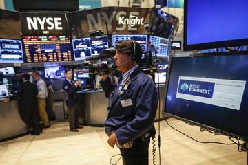 A cameraman prepares to shoot video before the opening bell at the New York Stock Exchange in Lower Manhattan, New York