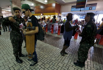 Brazilian Army soldiers distribute pamphlets with information to combat the Aedes aegypti mosquito during the National Day of Mobilization Zika Zero at Central train station in Rio de Janeiro,