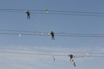 Workers of Torrent Power Limited remove kites tangled up in electric power cables after the end of the kite flying season in Ahmedabad