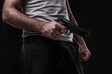 Killer with gun on black background at the studio