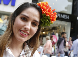 A woman wears flowers in her hair during the annual carnival celebration of the start of the spring season in Adana city